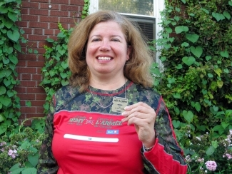 Image of Linda Paul holding her metal tags from the Army Run 5k event standing in front a house with bushes