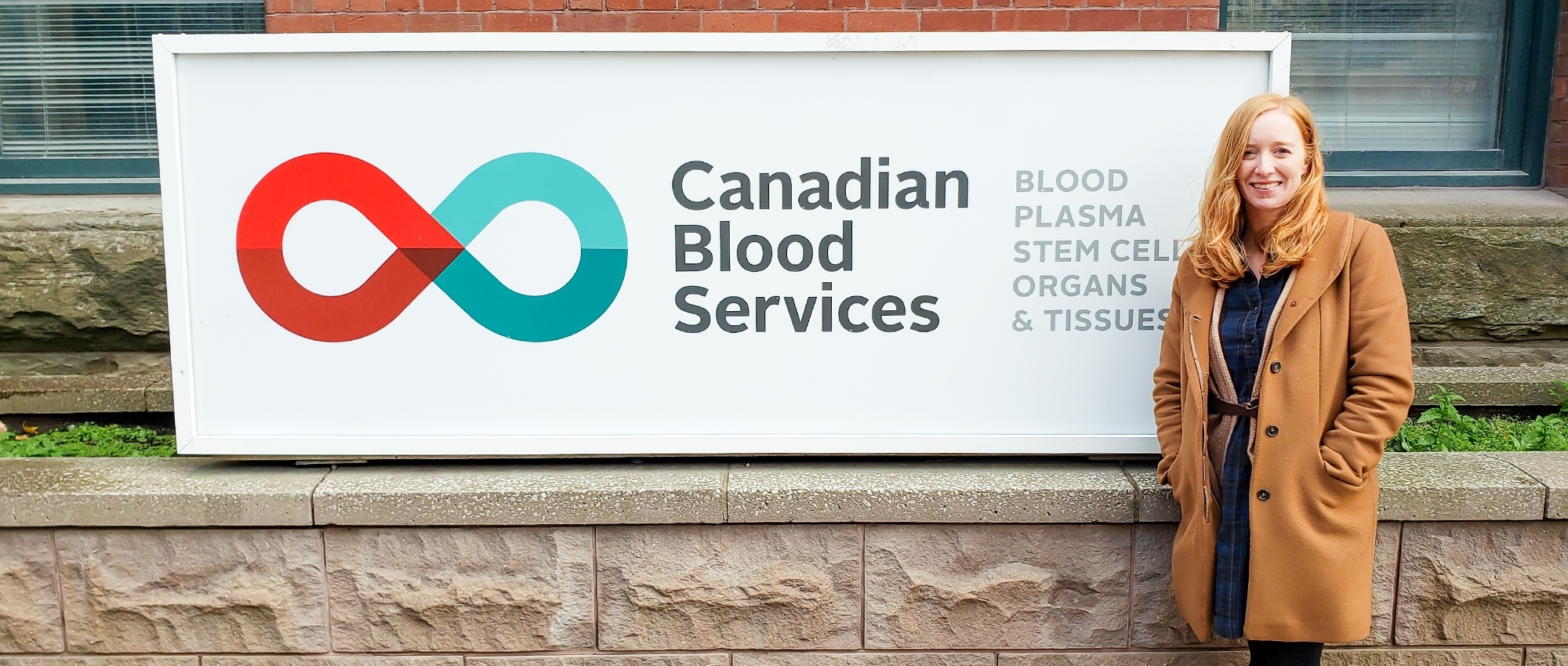 Dr Kelly Holloway standing beside a Canadian Blood Services Sign outside