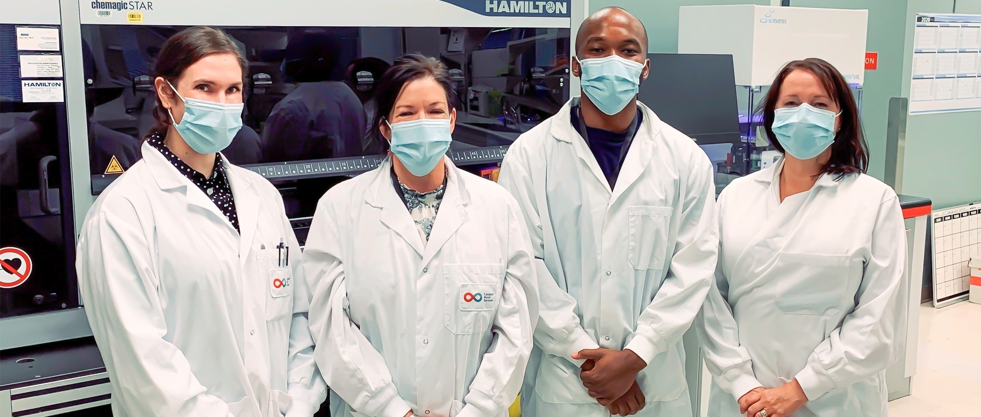 Featured image of lab team members Stacey Vitali, Carissa Kohnen, Andy Tshiula Kalenga and Valerie Conrod standing together in front of a Hamilton machine wearing masks.