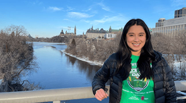 A woman in a green shirt stands on a bridge in Ottawa