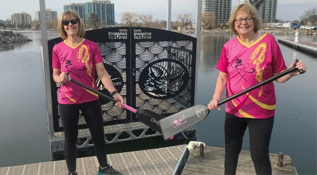 Breast cancer survivors and dragon boat team members Vonnie Pope and Donna Jelly with paddles near the water.